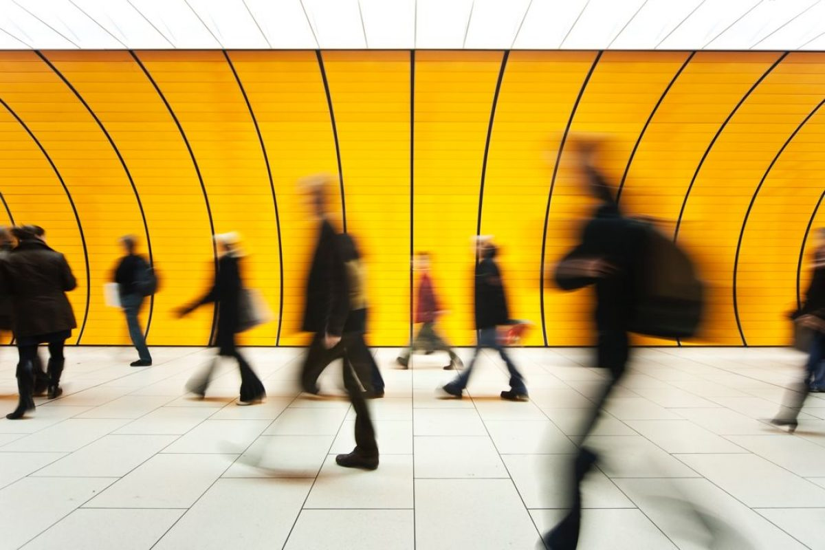 People-blurry-in-motion-in-yellow-tunnel-down-hallway-157531192_5616x3744